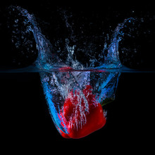 Close-up Of Red Bell Pepper Splashing Water Against Black Background