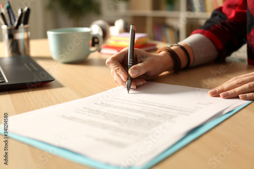 Cuadros en Lienzo Student girl hand signing contract at night