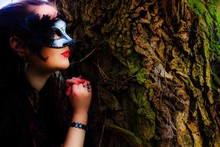 Close-up Of Woman Wearing Venetian Mask While Leaning On Tree