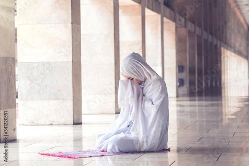 Fotografia Young muslim woman praying in the mosque