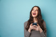 Photo of excited nice woman smiling and using cellphone