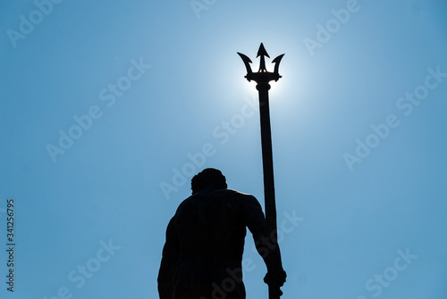 Photo Neptune statue with trident covering the sun