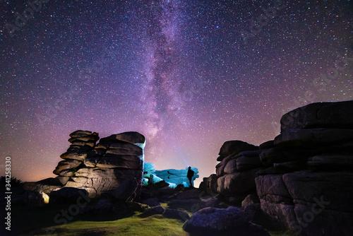 Silhouette of figure stargazing in rocky landscape below a clear night sky & vib Canvas Print