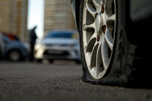 Car Tire With A Flat Tire In The Yard Near A Multi-storey Building. Image Of An Accident, Damage, Breakdown For Illustration On The Topic Of Repair, Insurance. Blurred