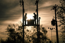 Low Angle View Of Silhouette Workers Standing On Electricity Transformer During Sunset