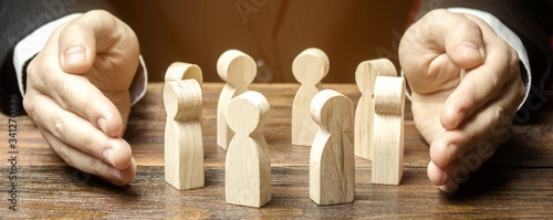 Obraz Businessman defending his team with a gesture of protection. Care for employees. Life insurance. Security and safety in a business team. Human resources. Social protection. Wooden figures - fototapety do salonu