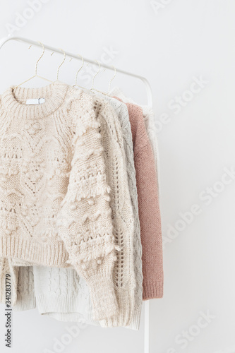 Casual knitted sweaters hanging on a rack Wall mural