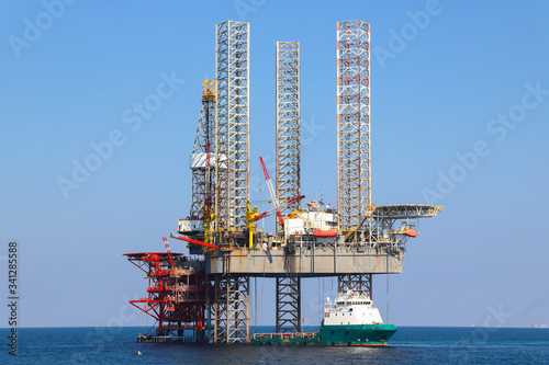 Photo Offshore oil platform and supply ship are in Persian Gulf.