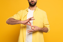 Cropped View Of Man Showing Interpretation Sign In Deaf And Dumb Language On Yellow Background