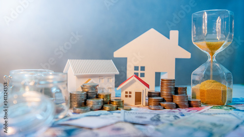 Fototapeta Saving money for retirement concept. Real estate or property investment. Home mortgage loan rate. Coin stack, money bag and currency glass jars on banknotes with hourglasses, house model on the table. obraz