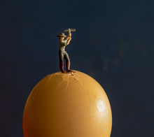 Close-up Of Figurine Breaking Egg With Hammer Against Black Background
