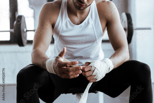 cropped view of bearded sportsman wrapping hand in sports bandage Canvas Print