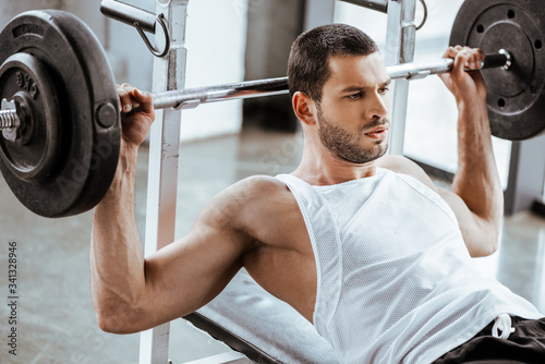 Fotografie, Tablou handsome sportsman working out with barbell in gym