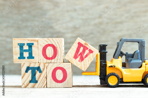 Photo Toy forklift hold letter block w to complete word how to on wood background