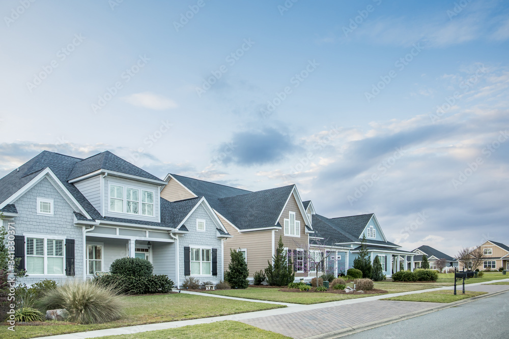 A street view of a new construction neighborhood with larger landscaped homes and houses with yards and sidewalks taken near sunset with copy space