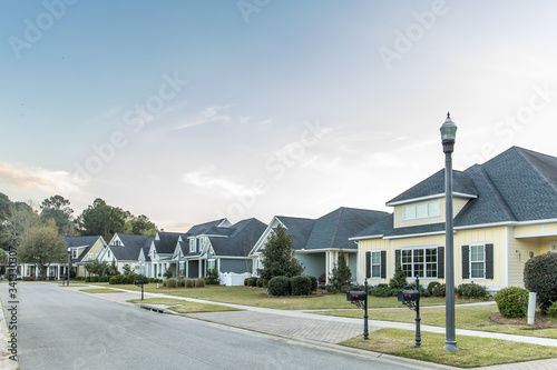 A street view of a new construction neighborhood with larger landscaped homes an Slika na platnu