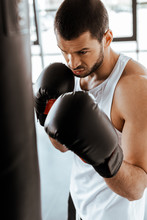 Selective Focus Of Athletic Man In Boxing Gloves Training With Punching Bag