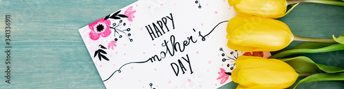 Photo panoramic shot of greeting card with happy mothers day lettering near yellow tul