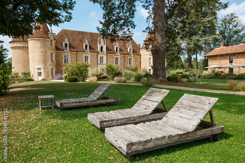 Wooden sunbeds standing on the background of old chateau Poster Mural XXL