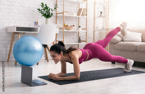 Obraz Sports during quarantine. Beautiful girl participating in online fitness class via laptop at home - fototapety do salonu