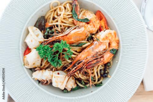 Valokuvatapetti drunken spaghetti with seafood on white plate is modern Thai fusion food