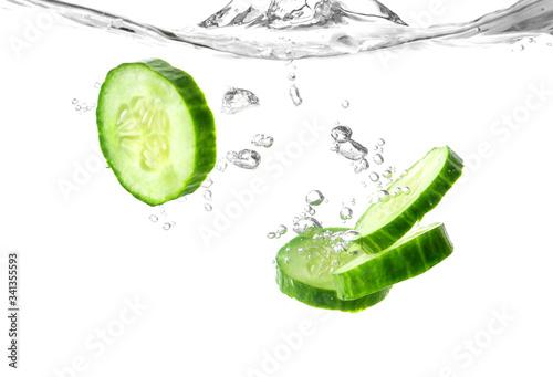 Fototapeta Falling of fresh cucumber slices into water against white background obraz