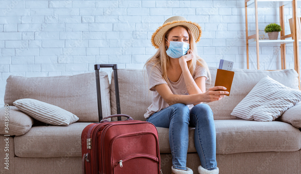 Fototapeta Sad girl in mask with tickets and suitcase
