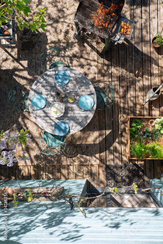 To view, a table set up on a beautiful flowered terrace awaits the guests of the BBQ Canvas Print