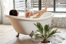 A Gorgeous Woman Is Enjoying Herself In A White Bathtub, In A Bright Room With A Large Window.