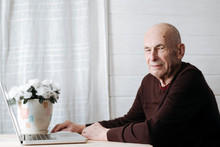 Portrait Of Smiling Old Man Sitting At Table With Laptop