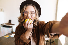 Image Of Joyful Woman Smiling And Eating Apple While Taking Selfie