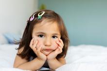 Portrait Of Bored Little Girl Lying On Bed