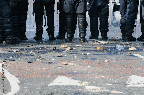 Fotografiet Stones and bricks litter the road as police riot squad move forward after a crow
