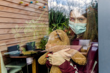 Portrait Of Girl With Surgical Mask And Teddy Bear Behind Window Pane