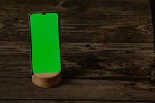Phone With A Green Screen Lies On An Old Wooden Table