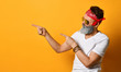 Mature male in sunglasses, red bandana, white t-shirt, bracelet. Pointing at something by forefingers, posing on orange background