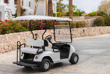 The Golf Cart Is Parked Next To A Flower Bed. The Electric Car Is Located Near The Tourist Hotel. There Is An Empty Pleasure Car On The Sidewalk.