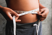Midsection Of Overweight Person Measuring Waist With Tape
