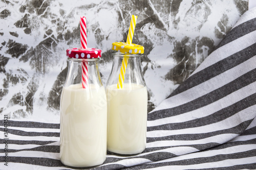 Bottle of fresh milk on table with kitchen towel