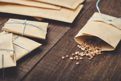 Fototapeta Paper bags with seeds for planting. Sprinkled radish seeds. Wooden table. obraz