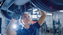 Portrait Shot Of A Female Mechanic Working Under Vehicle In A Car Service. Empowering Woman Wearing Gloves And Using A Ratchet Underneath The Car. Modern Clean Workshop.