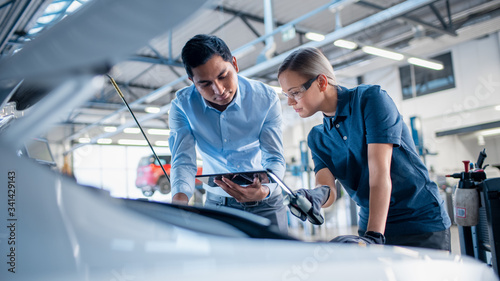 Instructor with a Tablet Computer is Giving a Task for a Future Mechanic. Female Student Inspects the Car Engine. Assistant is Checking the Cause of a Breakdown in the Vehicle in a Car Service.