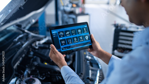 Car Service Manager or Mechanic Uses a Tablet Computer with a Futuristic Interactive Diagnostics Software Canvas Print