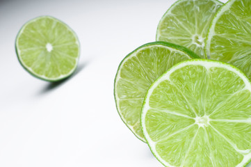 Various slices of green lemon over a white background.