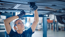 Portrait Shot Of A Female Mechanic Working On A Vehicle In A Car Service. Empowering Woman Wearing Gloves And Using A Ratchet Underneath The Car. Modern Clean Workshop.
