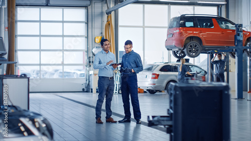Fototapeta Manager Checks Diagnostics Results on a Tablet Computer and Explains a Vehicle Breakdown to a Handsome Mechanic. Car Service Employees Talk while Standing in a Garage. Modern Clean Workshop. obraz