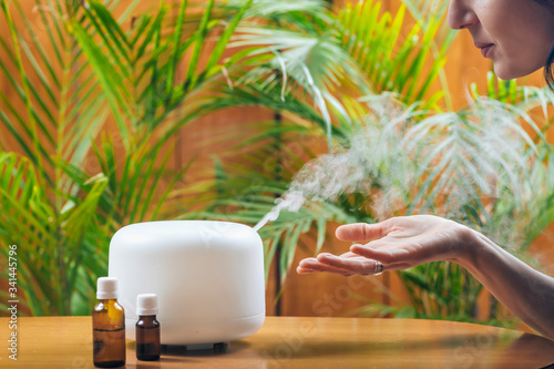 Fotografie, Tablou Woman Enjoying Aroma Therapy Steam Scent from Home Essential Oil Diffuser or Air