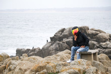 Full Length Of Man Wearing Helmet While Sitting On Rock By Sea Against Sky