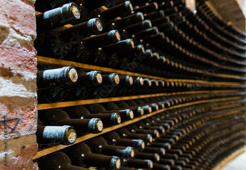 Foto Red wine bottles stored in a wine cellar of a winery