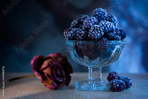 Photo Frozen blackberry in a vase in the moonlight on a table, next to a dried rose on